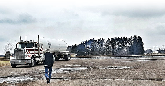 Truck Owner / Operator walking across the parking lot to his rig hauling a commercial propane tanker
